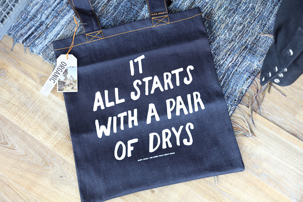 A tote bag reveals Nudie's origins when it started out producing 'dry' jeans.