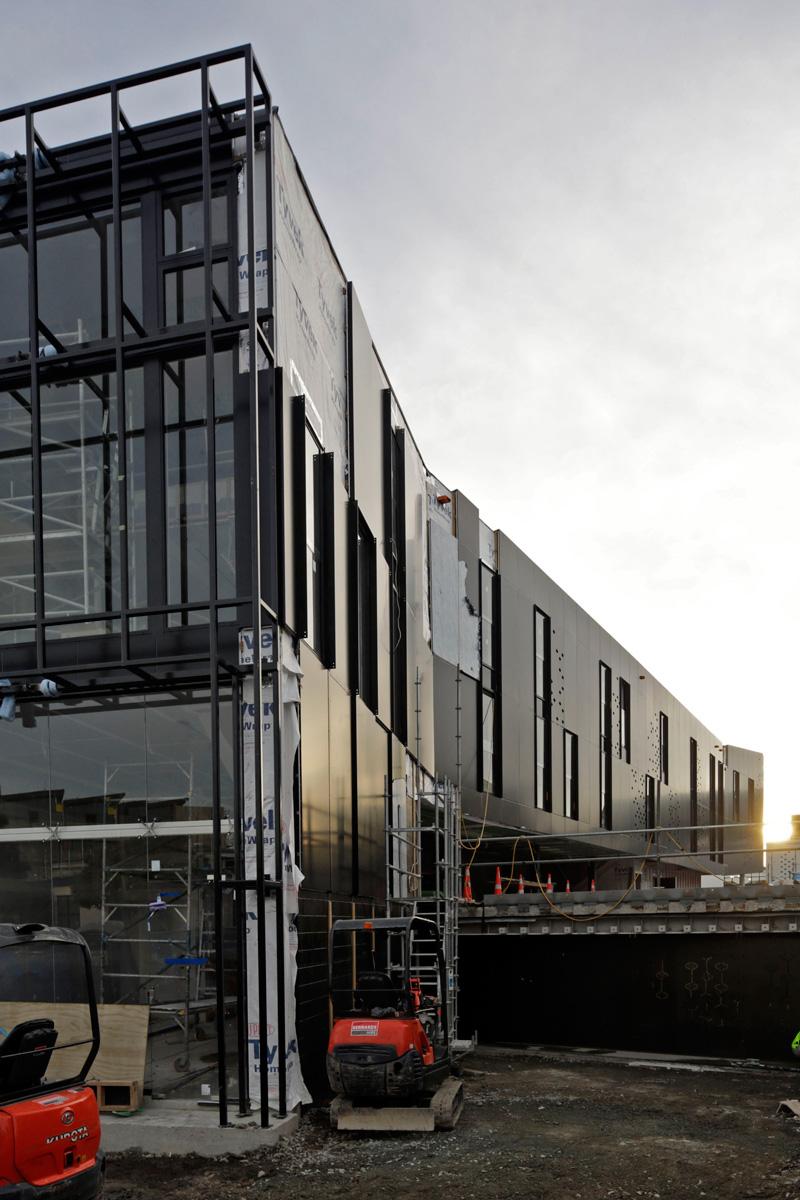 The new building kicks up at one end and kinks sideways at the other.